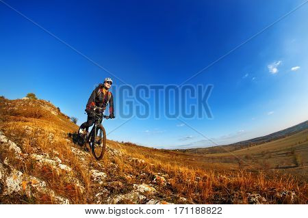 Wide angle view of a cyclist riding a bike on a nature trail in the mountains. people living a healthy lifestyle. Cyclist with helmet and gjasses. Beautiful landscape with hill and blue sky. Spring season. Travel in the countryside.