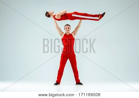 The two gymnastic acrobatic caucasian men posing in balance posture on gray studio background