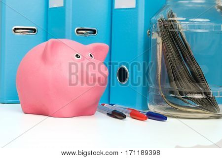 piggy bank on the table in front of school subjects
