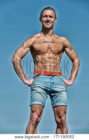 handsome man with sexy muscular body in shorts training sport has smiling happy face posing outdoor sunny summer on blue sky background