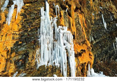 Steep rock with a frozen waterfall near the sea