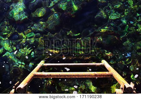 Iron stairs disappearing into the clear sea water and rocks on the bottom