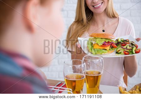 Smiled woman is giving the man a plate of food