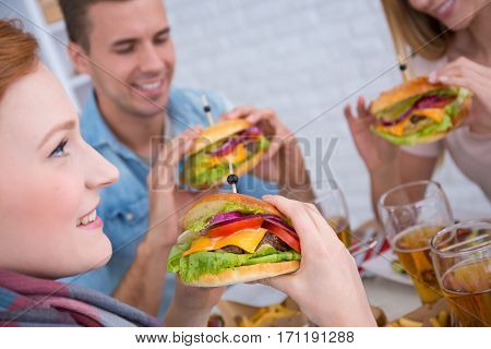 Smiled friends with burger in hand during meeting
