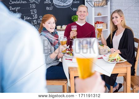 Man with a beer in his hand comes up to the table in a restaurant