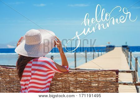 Closeup back view of woman in white hat looking out towards blue ocean and sky and words Hello summer. Calligraphy, lettering.