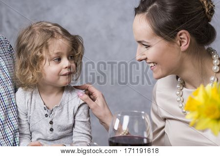 Young pretty woman smiling at her little daughter during dinner