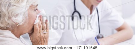 Older Patient Wiping Nose In The Doctor's Office