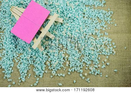 White Easel With Pink Paper For Inscriptions On The Crumbled Blue Gravel.