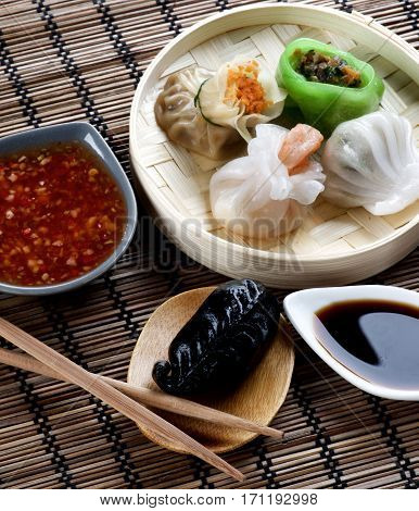 Assorted Dim Sum in Bamboo Steamed Bowl and Igaya with Seafood on Wooden Plate with Red Chili and Soy Sauces and Chopsticks closeup on Straw Mat background