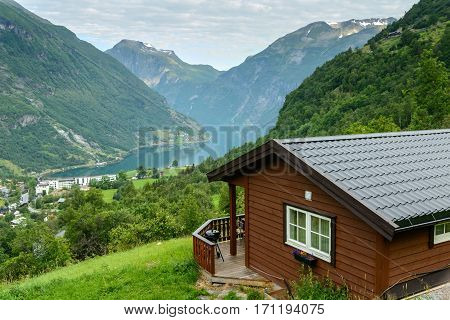 Beautiful view at fiord in a summer day with wooden cabin at foreground, Norway