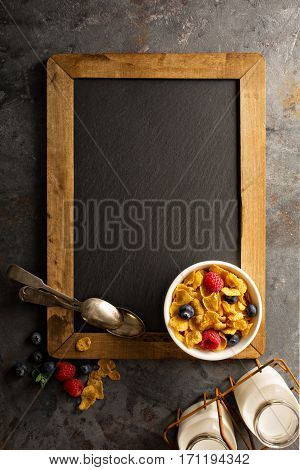 Healthy cornflakes with raspberry and blueberry in a bowl, quick breakfast or snack overhead shot