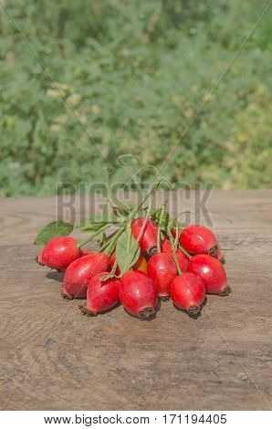 Hawthorn on wooden rustic table background. Rose hips haw fruit of the dog roses.