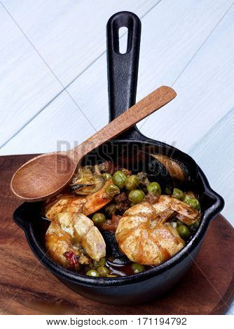 Delicious Seafood Curry with Prawns Mussels White Fish and Vegetables in Black Iron Cast Pot with Wooden Spoon closeup on Light Blue background