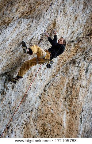 Rock climber, professional athlete, climbing in Siurana rocks, Spain. Extreme sports.