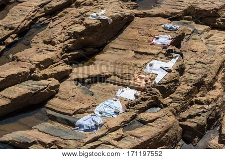 Drying clothes on the rocks in Srilankan village laundry at the mountain river
