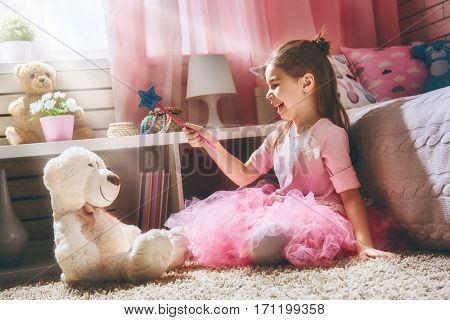 Happy girl plays with magic wand and teddy bear at home. Funny lovely child is having fun in kids room.