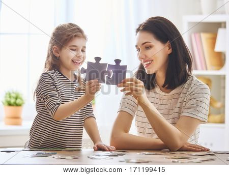 Happy family. Mother and daughter do puzzles together. Adult woman teaches child to solve puzzles.