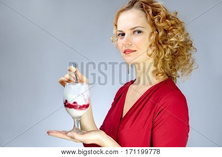 Beautiful playful young freckled girl with ice cream on blue background. portret close up