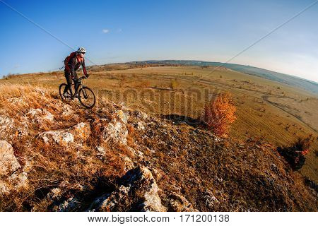 Wide angle view of a cyclist riding a bike on a nature trail in the mountains. people living a healthy lifestyle. Cyclist in the helmet and glasses. Fisheye. Landscape with hill, mound, horizon and blue sky.