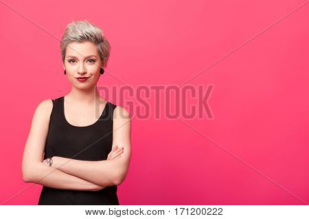 Close-up Portrait of young confident woman standing with arms crossed isolated over pink color background. Dyed blond short hairstyle