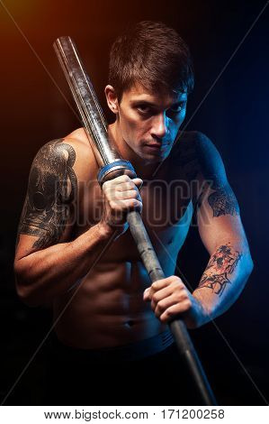 Strong muscular man with naked torso holding barbell. Sports, fitness concept.