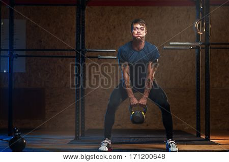 Male muscular athlete lifting kettlebell. Weightlifting workout. Sports, fitness concept
