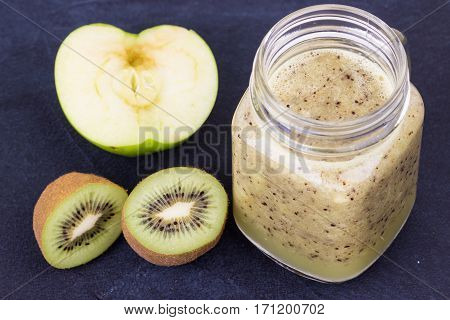 Kiwi and apple smoothie in glass bottle on blue background. Selective focus.