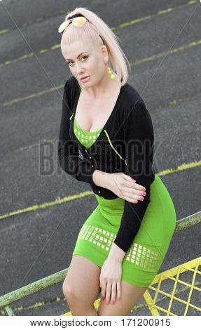 the woman in green sits on a protection at a racetrack a subject beautiful women