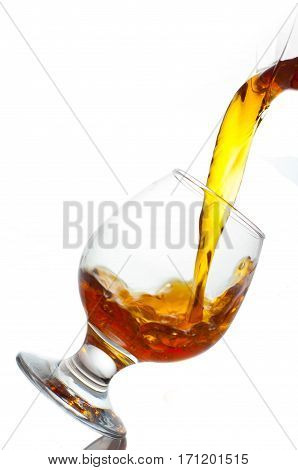 The glass is poured brandy on a white background
