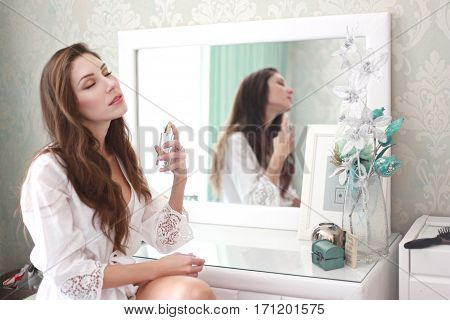 Focus on hand with parfume half length portrait of beautiful young woman sitting on the chair in the bedroom and using parfume