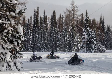 Athletes on a snowmobiles moving in the winter forest in the mountains of the Southern Urals.
