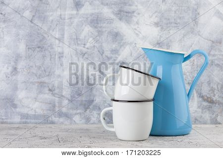 Two white enamel mugs and blue pitcher on light background