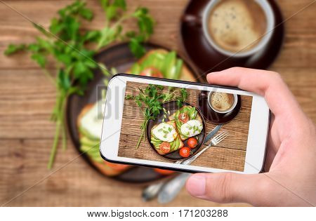Hands taking photo sandwich with avocado and poached egg with smartphone.