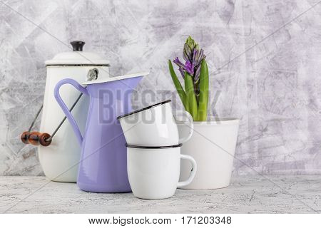 Two white enamel mugs violet jar white can and blossoming flower hyacinth in pot on light background