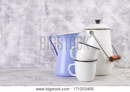 Two white enamel mug violet jug and white can on light background