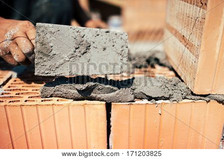 Details Of Industrial Bricklayer Installing Bricks On Construction Site