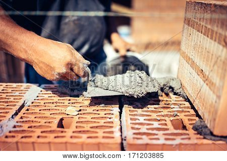 Close Up Details Of Industrial Bricklayer Installing Bricks On Construction Site..