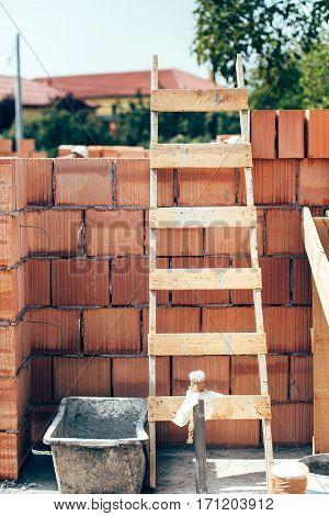 Wooden Ladder On Building Construction Site. Details Of Masonry And Wooden Tools