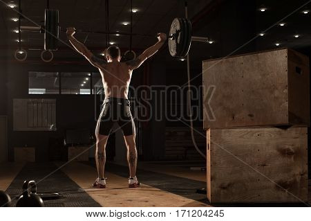 Young muscular man lifting barbell over head. Male athlete with naked torso doing weightlifting workout. Sports, fitness - healthy lifestyle concept.