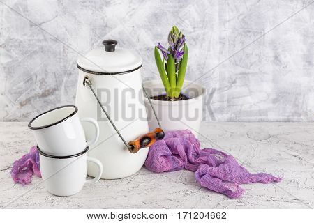 Two white enamel mugs white can and blossoming flower hyacinth in pot on light background