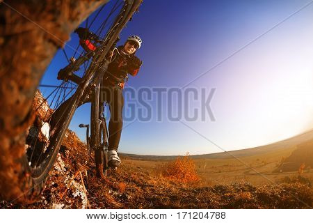 low angle view of cyclist standing with mountain bike against bright sun and blue sky. sping season. Horisontal wide angle fisheye photo. travel in the countryside. Beautiful nature landscape.