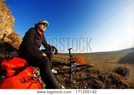 Man in a bike helmet makes a break. Travel in the countryside in spring time. Cyclist in the helmet with red backpack. Make a break.