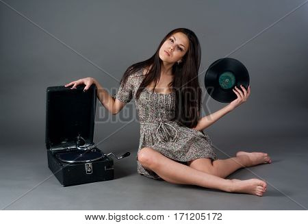 Beautiful woman with gramophone over grey background