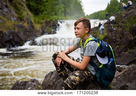 Portrait of a boy standing near a waterfall in the summer