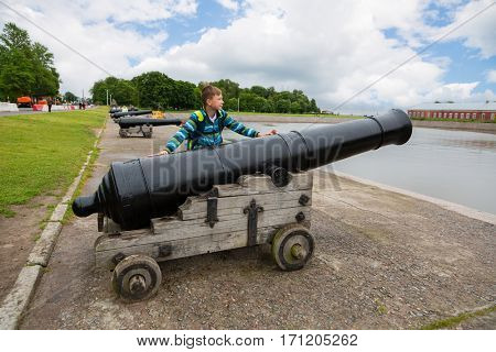 Teenager standing near an old cannon on the embankment in Kronstadt, Russia.