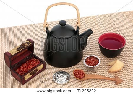 Safflower herbal tea with oriental teapot, cup, strainer, old wooden caddy and spoon with fortune cookie on bamboo over white background. Used also in chinese herbal medicine.