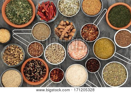 Herb and spice seasoning for cooking in scoops and bowls forming a background, high in antioxidants and vitamins.