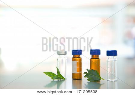 glass vial with green leave in science laboratory on white light