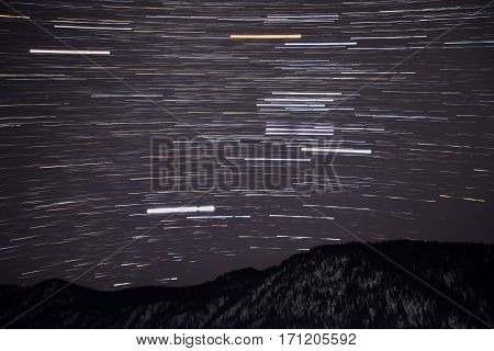 Beautiful night view with traces of stars in the form of tracks in the night sky on the background mountains with snow shot with a long exposure